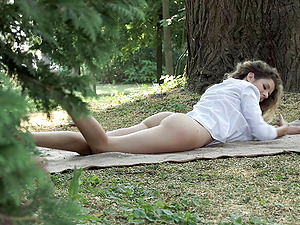 Teenage beauty with curly hair masturbates in the grass