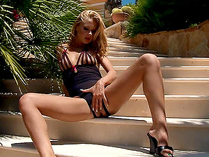 Blonde long-haired stunner fondles her clitoris and pisses on the stairs