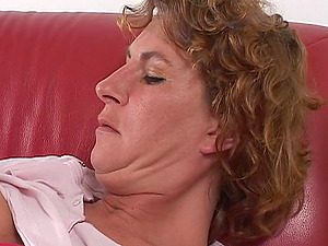 Suzie gets comfy on a leather sofa and starts pleasing herself
