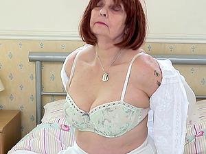 Mature amateur redhead British granny Jade strips at home