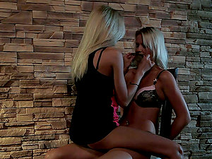 Andrea Francis and Clara G. have fun with a strap on indoors