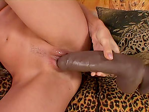 Horny Sophie Paris plays with her humid beaver on a sofa