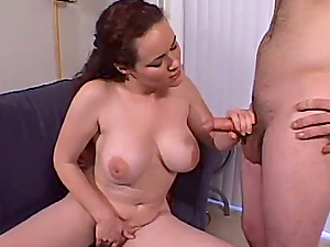 Curly dark-haired dame with tasty hooters gives a handjob