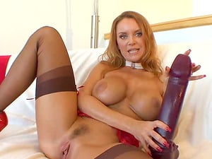 Redheaded cougar pumps a gigantic faux-cock deep into her vagina