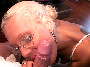 A blonde with glasses on her knees nursing on a dick