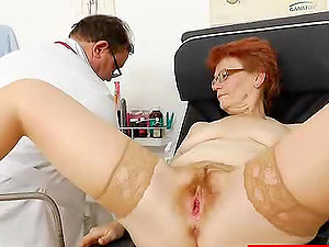 Gynecologist looks inwards the vagina of his mature redheaded patient