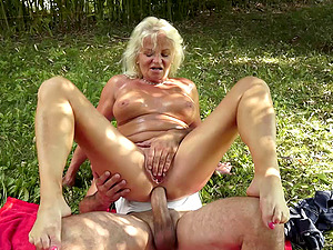 Mature woman sunbathes and fucks while out by the lake