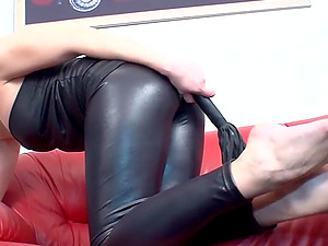 Attractive dame in leather attire loves when sub licks her high-heeled shoes