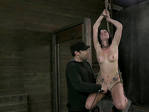 Black-haired cutie attempts to smile during the painful restrain bondage activity
