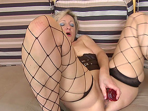 Inviting granny delights her moist twat with a crimson fake penis