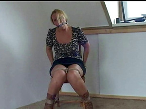 Busty honey Deedee is topless, tied up and ballgagged on a chair