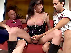 Horny black-haired shemale fucks two guys on the sofa