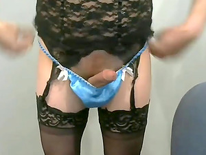 Horny crossdresser in sexy lingerie and blue panties is masturbating