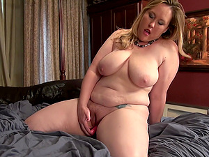 Mature amateur buxom MILF Caitlin spreads her pussy on the bed