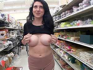 Darh haired Lexi has fun with vegetables in a public store