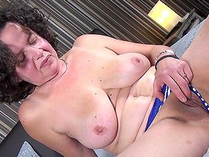 Curly haired buxom mature amateur MILF Tanja K. masturbates