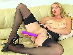 Solo matur British MILF masturbates on a couch at her house