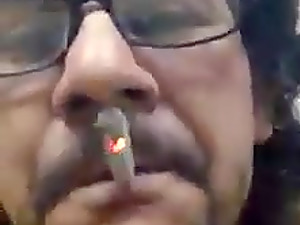 Jed pulls on cigarette smoke while jerking off his dick