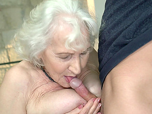 Horny older madam Norma seduced her neighbor and fucked him on the couch