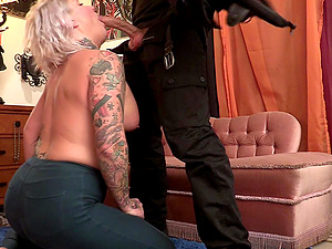 Tattooed mature with fake tits drops on her knees to suck a dick