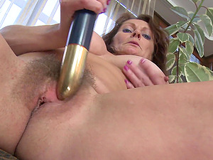 Busty mature amateur flashes her boobs and plays with her gold dildo