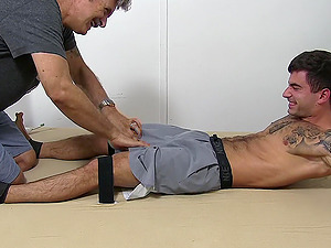 Tied up guy with a small cock enjoys while an older guy tickles him