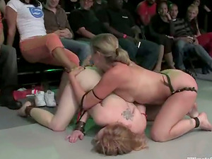 Horny and nude chicks fight in a ring to please their admirers