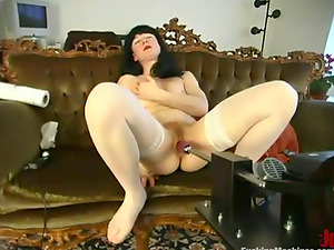 Dark-haired Lulu gets drilled by a machine on a sofa